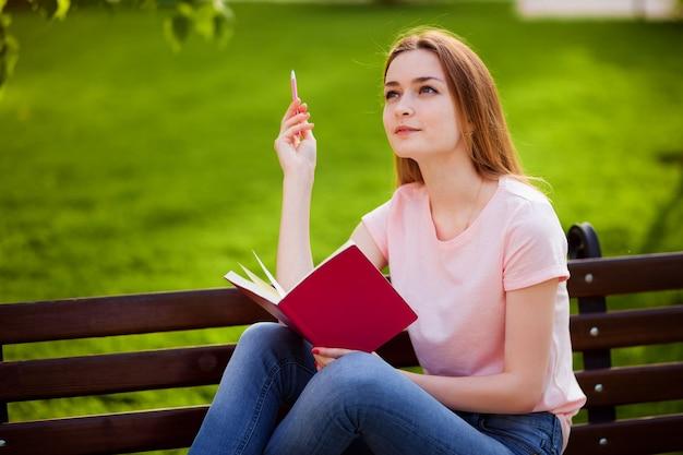Fille pense quoi écrire dans un cahier, assis dans le parc