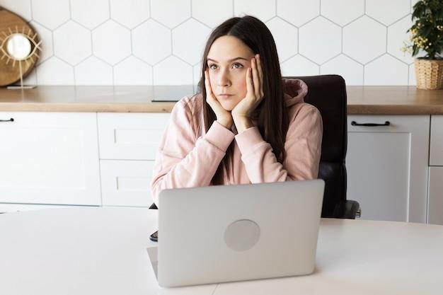 Fille pensive au travail à l'ordinateur, travail à domicile en ligne