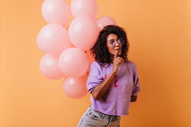 Fille pensive avec bouquet de ballons de fête posant sur orange. dame glamour célébrant son anniversaire.