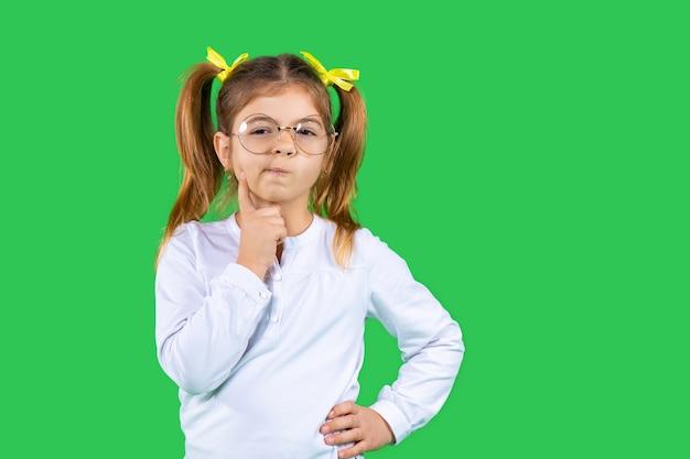 Une fille pensive avec des queues de cheval et des lunettes tient sa main sur son visage et regarde l'appareil photo vert