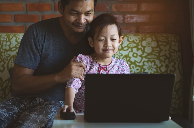 Fille et père apprenant et jouant à l'ordinateur à la maison