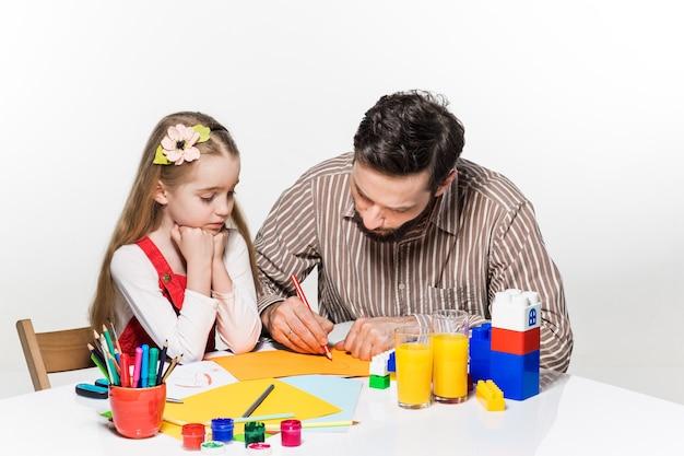La fille et le père dessinent et écrivent ensemble sur fond blanc