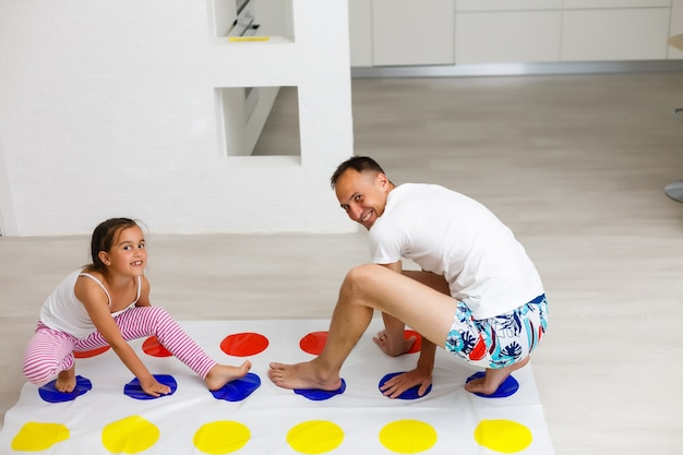 Fille et père jouent au twister à la maison