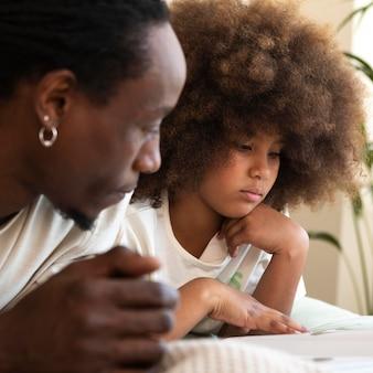 Fille et père lisant un livre ensemble