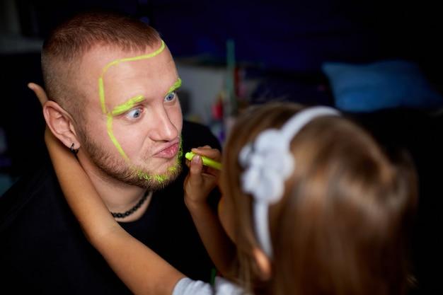 Fille et père peignent un visage, s'amusant