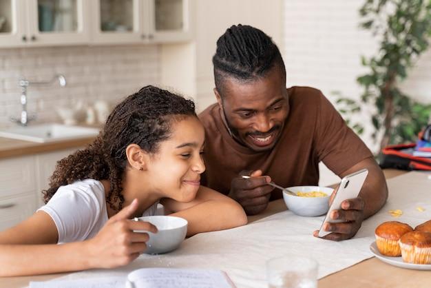 Fille et père regardant une vidéo au téléphone