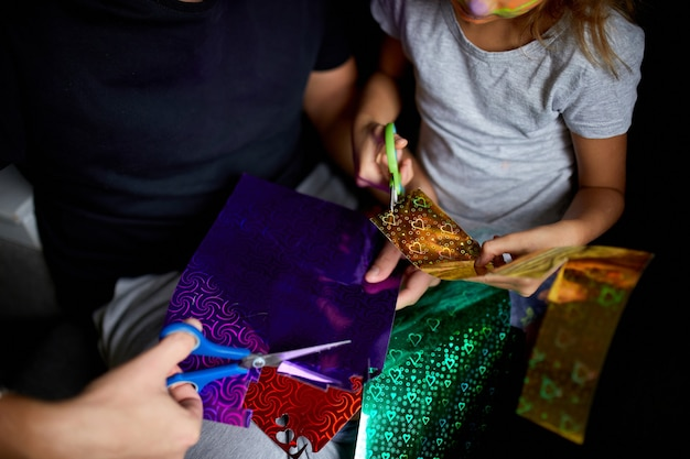 Fille et père s'amusant à faire de l'artisanat ensemble à la maison sur le canapé, couper un papier avec des ciseaux, lumière sombre,
