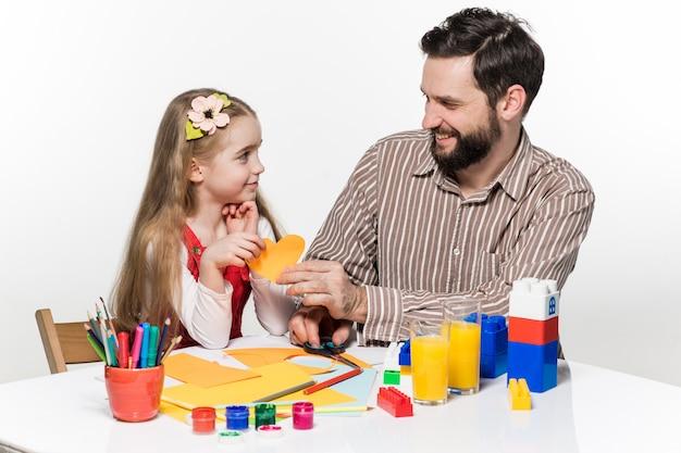 La fille et le père taillant des demandes papier