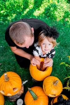 La fille et le père tirent les graines et le matériau fibreux d'une citrouille avant de sculpter pour halloween. prépare un jack-o-lantern. décoration pour la fête. famille heureuse. petite aide. vue de dessus.