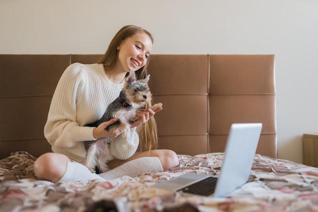 Une fille avec un petit chien communique à la maison via webcam