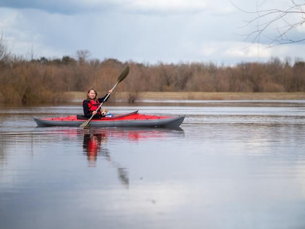 Une fille et un petit chiot naviguent sur un kayak.