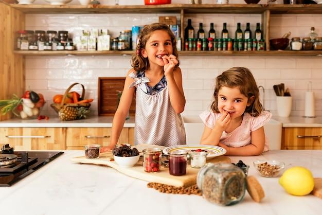 Fille de petites sœurs préparant des biscuits. concept de chef infantile.