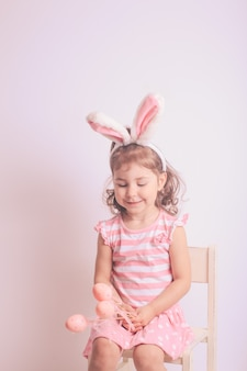 Fille avec de petits oeufs roses pour la chasse de pâques