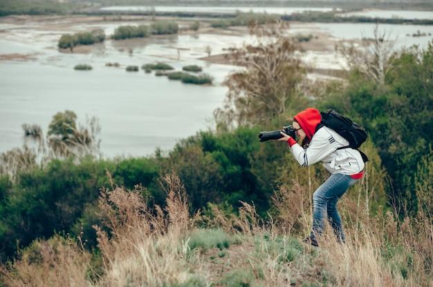 Fille photographiant la nature debout au bord de la falaise. vent froid.