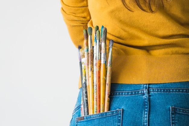 Fille avec des pinceaux dans la poche