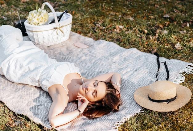 Fille sur un pique-nique avec un chapeau de paille au printemps dans le parc. brunette aux cheveux longs se trouve sur un plaid sur fond de nature estivale. jeunesse et beauté.