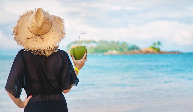 Fille sur la plage boit de la noix de coco.