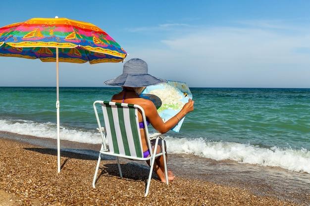 Fille sur la plage, bronzer, fille avec un ordinateur portable, femme sous un parapluie, chaise, parapluie, assiette, repos sur la mer, la mer noire, une journée ensoleillée, signe, téléphone, appareil photo, journal, magazine, carte, voyage