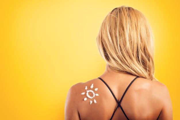 Fille à la plage en maillot de bain avec un soleil fait avec de la crème solaire
