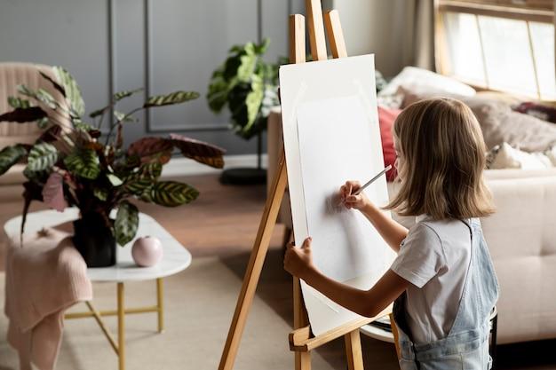 Fille de plan moyen dessinant à la maison