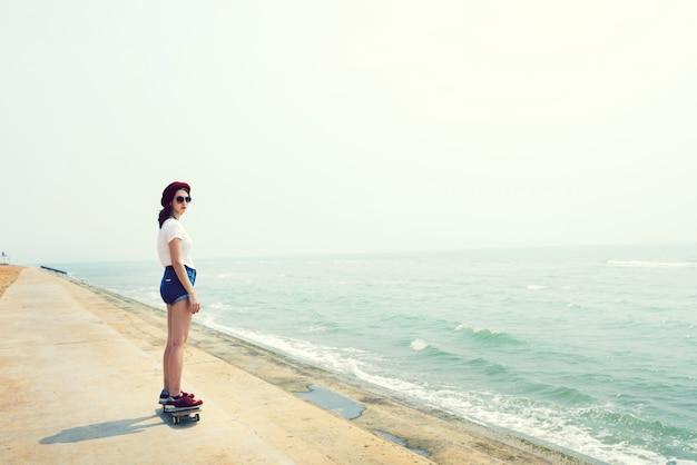 Fille sur la planche à roulettes de la plage