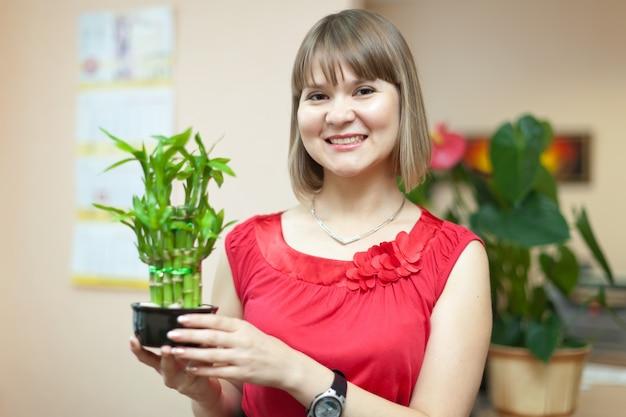 Fille avec une plante de bambou chanceuse