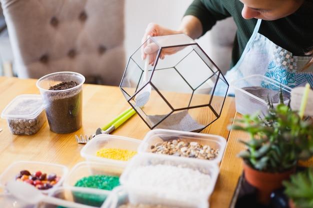 La fille plante une forme de verre, plante des fleurs, terarium de verre