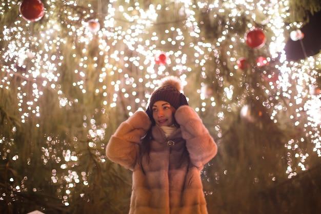 La fille en plein air dans la nuit du nouvel an ferme ses oreilles d'un salut