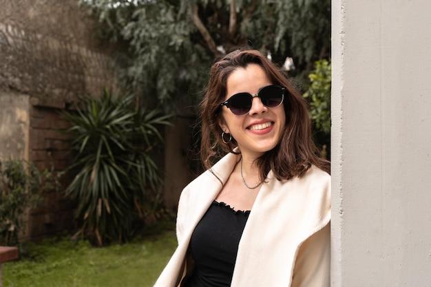 Fille en plein air avec des lunettes de soleil sombres s'appuyant sur une colonne et souriant