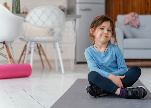 Fille de plein coup assis sur un tapis