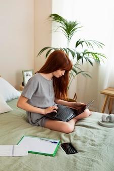 Fille pleine de coups apprenant avec un ordinateur portable