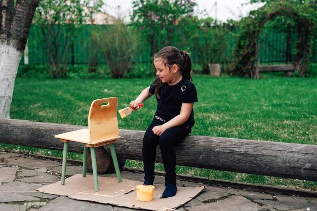 Une fille pleine d'enthousiasme peint une petite chaise dans le jardin sur une pelouse verte avec de la peinture jaune...