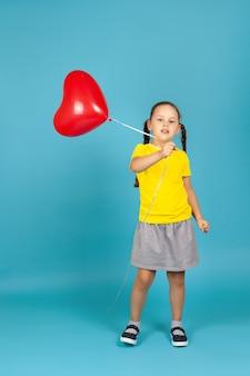 Une fille de pleine longueur danse et agite un ballon rouge en forme de coeur