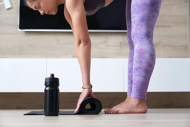 Fille Pliant Le Yoga Noir Ou Le Tapis De Fitness Après Avoir Travaillé à La Maison Dans Le Salon Yoga De La Vie Saine Photo Premium