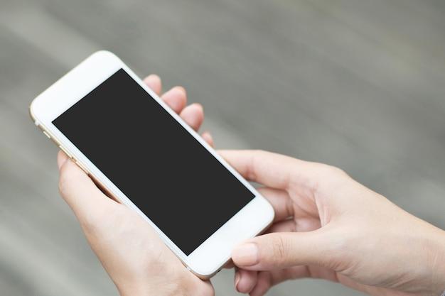 Fille pointant le doigt sur l'écran smartphone sur fond de plancher en bois dans la ville atmosphérique de nuit, hipster à l'aide de mains féminines et sms de téléphone mobile, mode de vie de rue de paillettes maquette