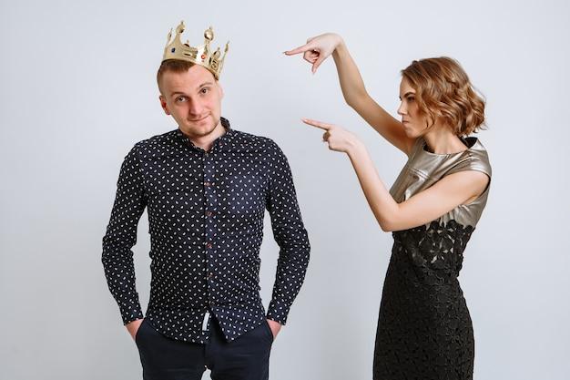 La fille pointe ses doigts vers la couronne, qui est posée sur la tête du gars.