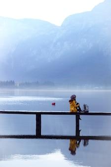 Fille sur un pont en bois sur un lac de montagne tôt le matin. beau paysage et reflet