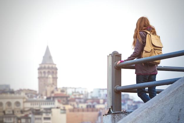 Fille sur le pont d'observation regarde istanbul. mosquée en arrière-plan