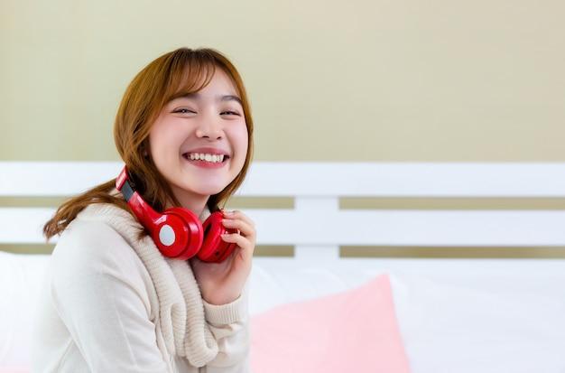 La fille portait des écouteurs et écoutait de la musique sur le lit.