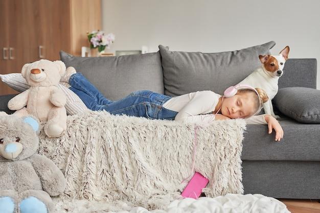 Fille portant sur un canapé dans les écouteurs, écouter de la musique avec son smartphone