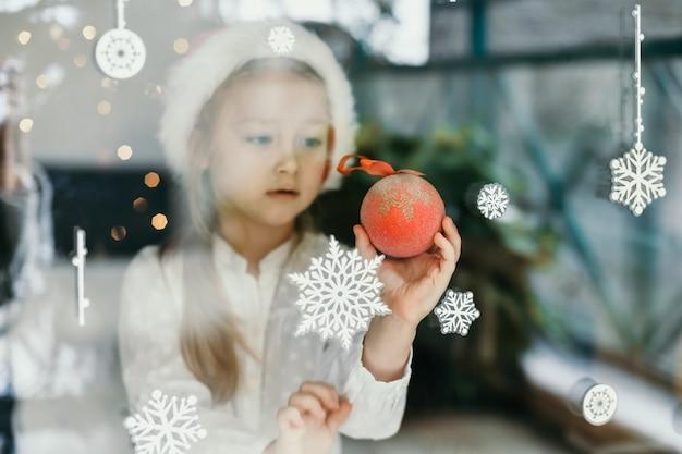 Une fille portant un chapeau de père noël regarde des flocons de neige sur la fenêtre