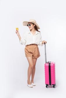 Fille portant un chapeau tenant une carte de crédit et une valise pour voyager