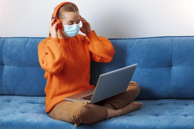 Une fille portant des écouteurs et un masque médical est assise avec un ordinateur portable sur le canapé à la maison