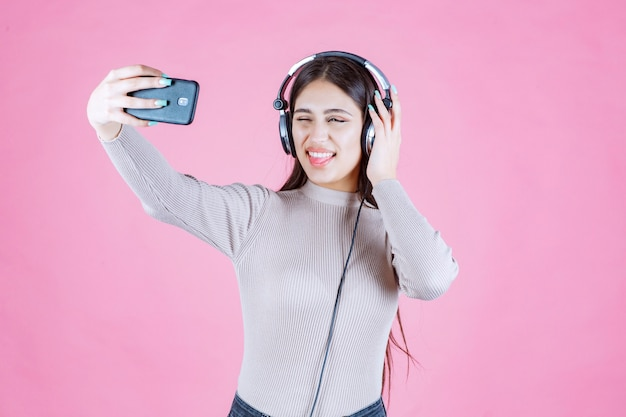Fille portant des écouteurs et prenant son selfie