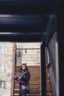 Une fille portant des lunettes en hiver porte des escaliers en bois