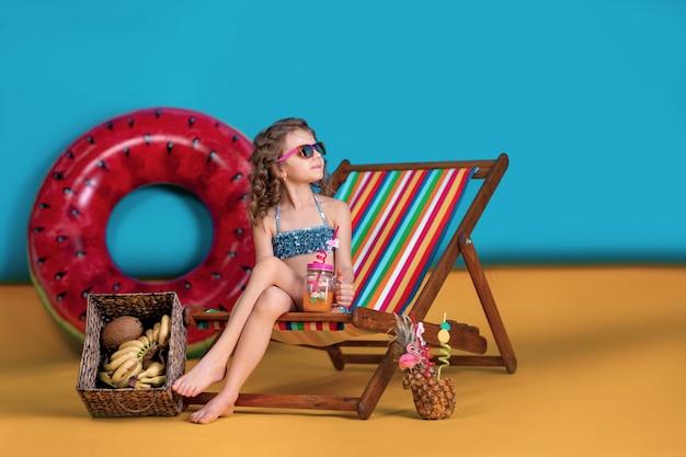 Fille portant un maillot de bain, lunettes de soleil tenant un pot avec du jus ou un cocktail avec des pailles multicolores assis dans une chaise longue arc-en-ciel par un grand cercle gonflable de pastèque et en regardant