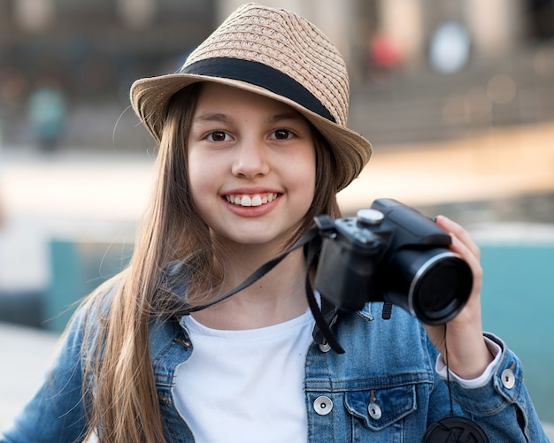 Fille portant un manteau en jean, un chapeau de paille et un jean avec appareil photo se promener dans le centre-ville et prendre des photos