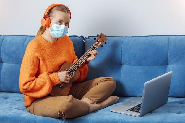 Une fille portant un masque médical est assise sur le canapé à la maison et apprend à jouer du ukulélé à distance