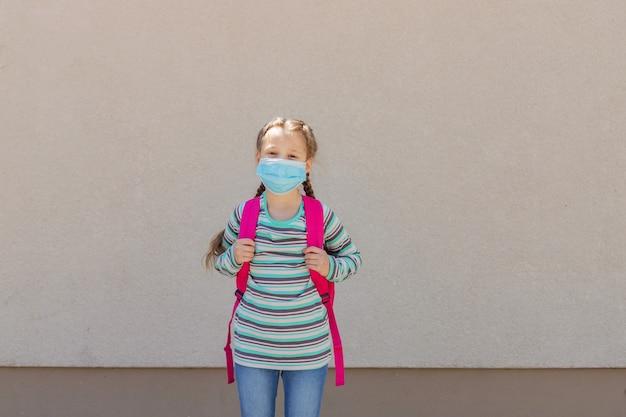 Fille portant un masque de protection avec un sac à dos derrière le dos dans la cour d'école