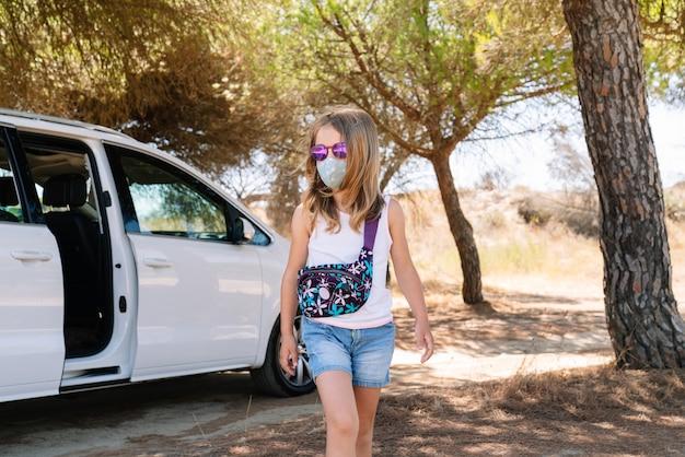 Fille portant un masque sur son visage et des lunettes de soleil roses marchant à travers les pins lors d'une halte de vacances au milieu de la pandémie de coronavirus covid19